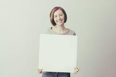 Ragazza con un cartellone pubblicitario bianco Immagine Stock