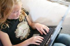Ragazza con un computer portatile Fotografia Stock