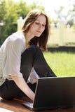 Ragazza con un computer portatile alla sosta Immagine Stock