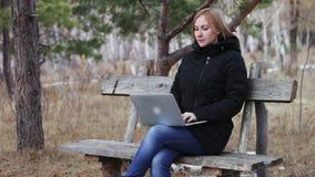 Ragazza con un computer portatile su un banco nel legno impianti all'aperto Foresta d'autunno archivi video