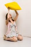Ragazza con un cuscino giallo Immagine Stock