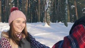 Ragazza con un giovane che sorride, camminante nella foresta di inverno, giorno soleggiato archivi video