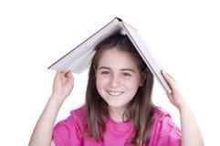Ragazza con un libro aperto sopra la sua testa Immagine Stock