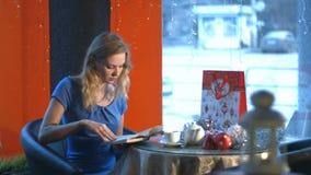 Ragazza con un libro in un caffè video d archivio