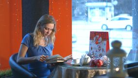 Ragazza con un libro in un caffè stock footage
