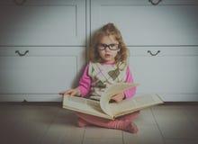Ragazza con un libro con i vetri sul pavimento, fotografia stock libera da diritti