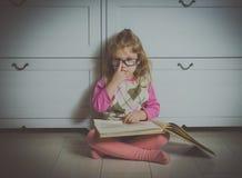 Ragazza con un libro con i vetri sul pavimento, fotografia stock