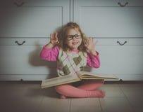 Ragazza con un libro con i vetri sul pavimento immagini stock