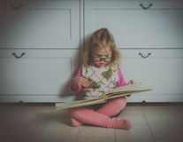 Ragazza con un libro con i vetri sul pavimento fotografie stock