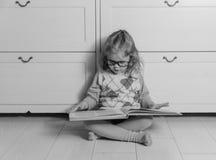 Ragazza con un libro con i vetri sul pavimento, in bianco e nero Fotografia Stock