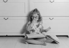Ragazza con un libro con i vetri sul pavimento, in bianco e nero Fotografie Stock Libere da Diritti
