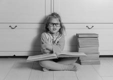 Ragazza con un libro con i vetri sul pavimento, in bianco e nero Fotografie Stock