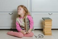 Ragazza con un libro con i vetri sul pavimento, in bianco e nero Fotografia Stock Libera da Diritti