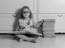 Ragazza con un libro con i vetri sul pavimento, in bianco e nero Immagine Stock
