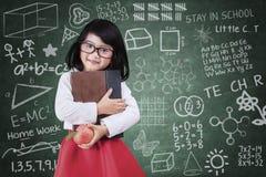 Ragazza con un libro e mela nella classe Fotografia Stock