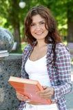 Ragazza con un libro nel suo sorridere delle mani Fotografie Stock Libere da Diritti