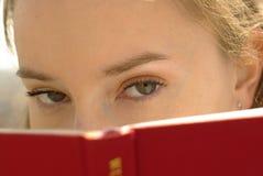 Ragazza con un libro rosso Fotografia Stock