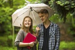 Ragazza con un libro rosso in sue mani ed il tipo con l'ombrello all'aperto Una conversazione delle coppie Immagine Stock