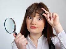 Ragazza con un magnifier in sua mano Fotografia Stock