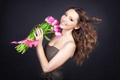 Ragazza con un mazzo dei fiori su priorità bassa nera Fotografie Stock