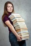 Ragazza con un mucchio dei libri Immagini Stock