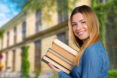 Ragazza con un mucchio dei libri Fotografia Stock