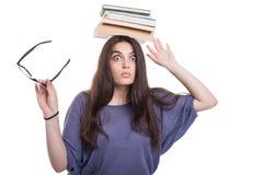 Ragazza con un mucchio dei libri sulla testa Fotografie Stock Libere da Diritti