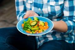 Ragazza con un piatto delle verdure in mani Immagini Stock