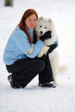 Ragazza con un Samoyed del cucciolo Fotografia Stock