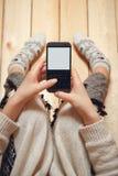Ragazza con un telefono in sue mani Immagine Stock