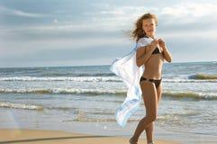 Ragazza con un tessuto su una spiaggia Fotografie Stock