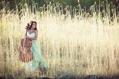 Ragazza con un violoncello in un'erba alta Fotografia Stock Libera da Diritti