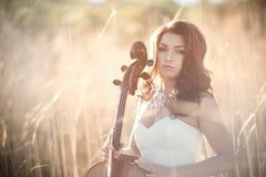 Ragazza con un violoncello in un'erba alta Immagine Stock