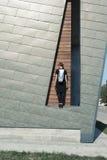Ragazza con una borsa sul fondo della parete Immagine Stock
