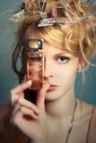 Ragazza con una bottiglia di profumo circa il suo fronte Fotografia Stock