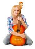 Ragazza con una chitarra che si siede su un bianco Immagini Stock Libere da Diritti