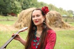 Ragazza con una chitarra e una rosa rossa in suoi capelli immagine stock