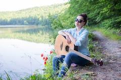 Ragazza con una chitarra nel lago della foresta Immagine Stock Libera da Diritti