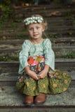 Ragazza con una corona dei fiori su lei seduta capa sulle scale fotografie stock