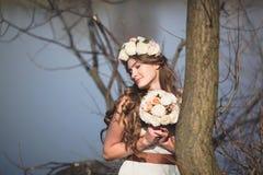 Ragazza con una corona floreale sulla testa che posa sul lago Immagine Stock