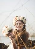 Ragazza con una corona floreale sulla testa che posa sul lago Immagini Stock