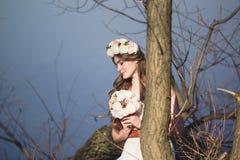 Ragazza con una corona floreale sulla testa che posa vicino all'albero Immagini Stock