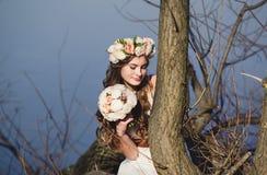 Ragazza con una corona floreale sulla testa che posa vicino all'albero Fotografie Stock Libere da Diritti