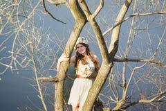 Ragazza con una corona floreale sulla testa che posa vicino all'albero Immagine Stock