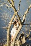 Ragazza con una corona floreale sulla testa che posa vicino all'albero Fotografie Stock