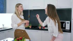 Ragazza con una forcella in sue mani che alimentano alla sua amica un'insalata di verdure, giovani donne che ridono allegramente  video d archivio