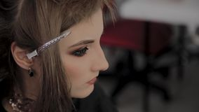 Ragazza con una forcella sui suoi capelli in un salone di lavoro di parrucchiere archivi video