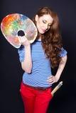 Ragazza con una gamma di colori e una spazzola Immagine Stock