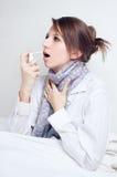 Ragazza con una gola irritata Immagini Stock