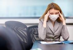Ragazza con una lavorazione a freddo nell'ufficio con la maschera Immagini Stock